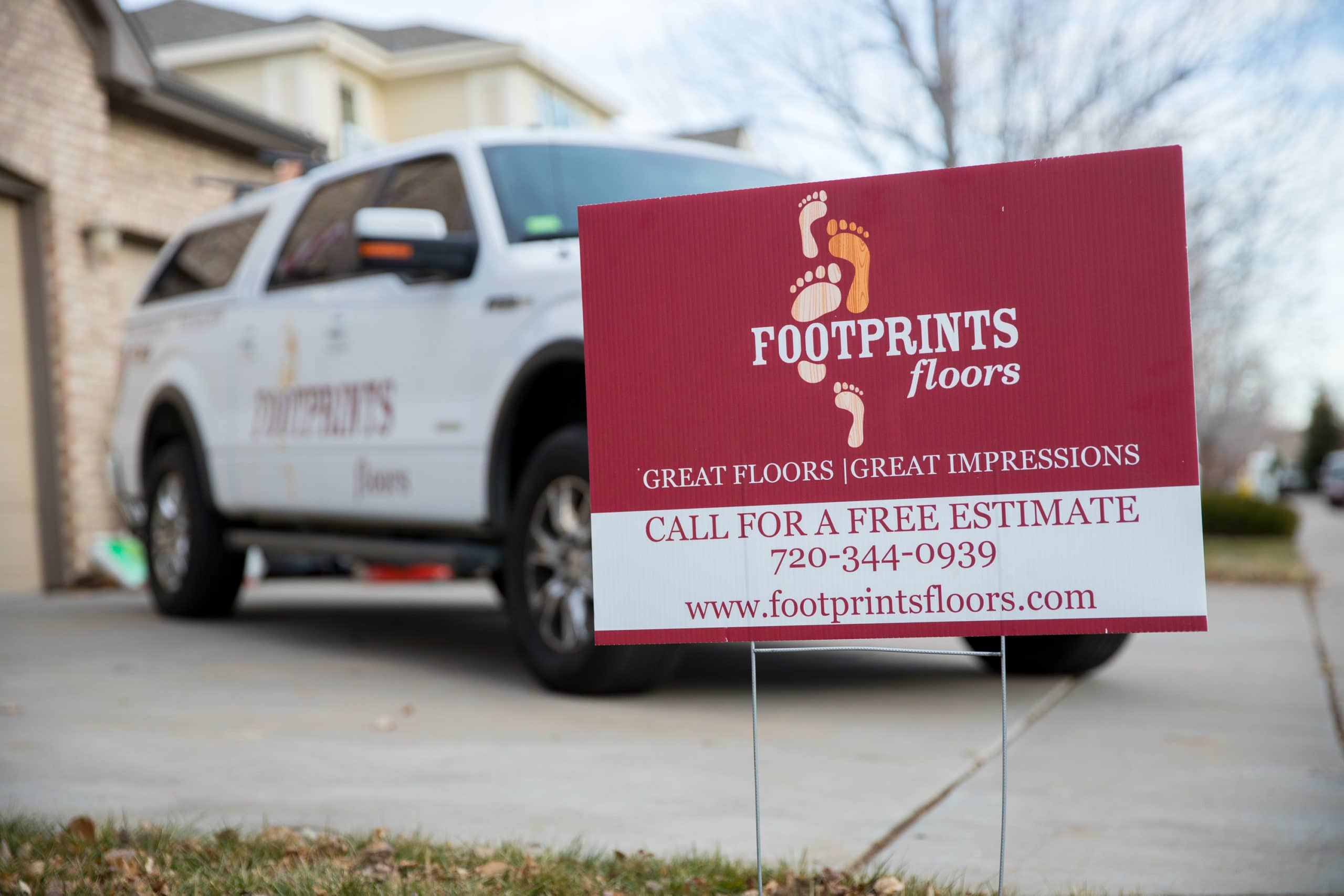 Footprints Floors sign in front yard demonstrates business growth and benefits of self-employment.